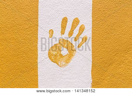 Hand print on orange and white wall
