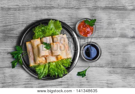 Little spring rolls on round metal tray plate light white surface lettuce parsley greens Fresh green onions soy sauce tomato sauce top view