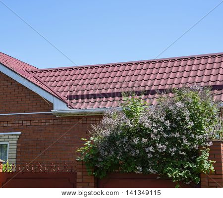 Facade Of A Brick Building With A Roof Made Of Brown Metal.