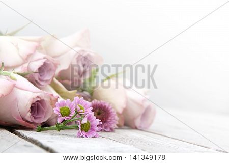 Still Life with pastel roses and daisies on a wooden table