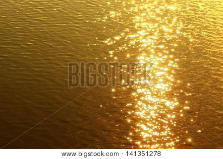 The light from the sunset Reflections on water Glitters is gold