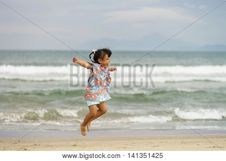 Small Girl Jumping With Happiness At China Beach In Danang
