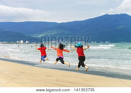 Women Jumping At China Beach Of Danang In Vietnam