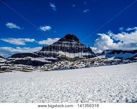 Mountain Looming over the snow field at Logan Pass