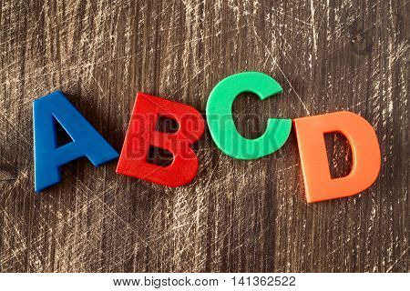 ABCD spelling from plastic letters on wooden background