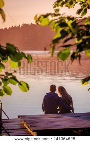 Rear view of a romantic young couple sitting on pier and enjoying stunning sunset near lake
