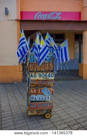 MONTEVIDEO, URUGUAY - MAY 04, 2016: nice little cart with a lot of car licenses and uruguay flags, cocacola banner as background.
