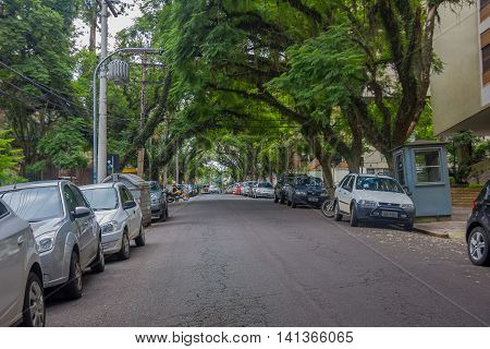 PORTO ALEGRE, BRAZIL - MAY 06, 2016: cars parked in the side of a nice street with trees in the sidewalks