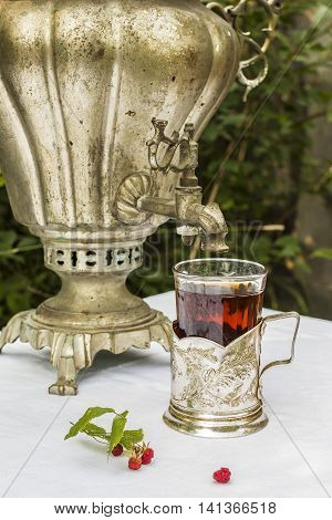 vintage copper samovar in a cup holder and a glass of hot tea close-up stands on the table beside are scattered fresh berries in a Russian village outdoors