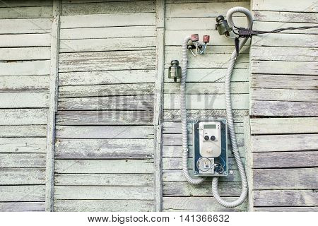 Modern electrical meter hanging on the old wooden house in the village outdoors