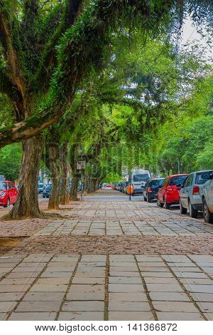 PORTO ALEGRE, BRAZIL - MAY 06, 2016: nice sidewalk with l, ot of trees on it, cars parked next to the sidewalk.