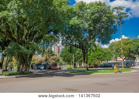 CURITIBA , BRAZIL - MAY 12, 2016: bus stations located in the middle of a park, big trees in front of the bus stations and some buildings as background.