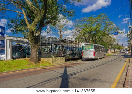 CURITIBA , BRAZIL - MAY 12, 2016: passengers getting on a public bus, big tree located next to the bus station.