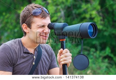 Man who is watching in spotting scope. Positive man looking through a telescope