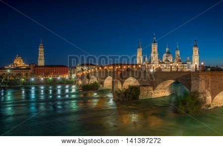 Basilica Our Lady Pillar In Zaragoza And the Bridge In Spain At Night Shot From Another Side Of The River View