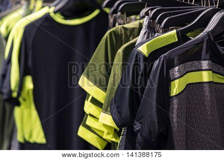 Close Up Of Men Black And Yellow Sports T-shirts Hanging On The Rail Inside The Clothing Outlet Close Up Picture