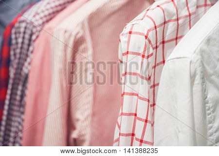 Assortment Of Classic Man Shirts With Geometric Patterns Hanging On The Rail Indoors Close Up Pic