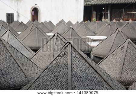 Large soy sauce urns outside covered in rattan hats within Wuzhen town in Zhejiang province China.