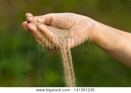 sand running through hand on green blurred background