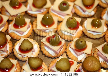 Closeup of crackers with cheese ham olives and ketchup.