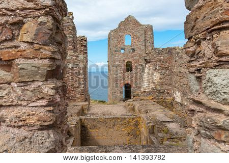 Industrial ruins a reminder of past old stone intrior remains Wheal Coates Tin Mine engine house on Cornwall coast United Kingdom