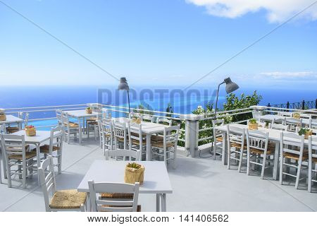 Luxury terrace balcony of exclusive seaside resort with fancy table and chairs fuit and flower bawl and full sea panorama in the beautiful morning lights