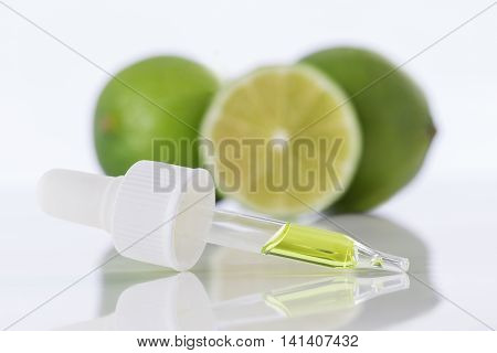 Aromatherapy essential oil bottle with lime fruit and leaf sprig.