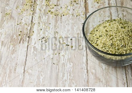 Bowl Of Raw Shelled Hemp Seeds On A Wood Plank Board
