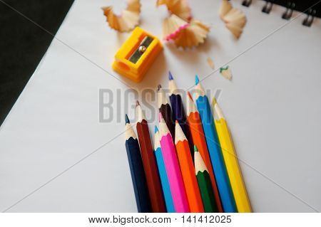 sharpened colored pencils, sharpener and shavings on a white notebook