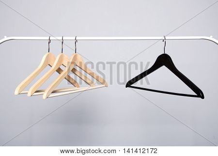 Three beige and one black clothes hangers hanging opposite each other on a white crossbar