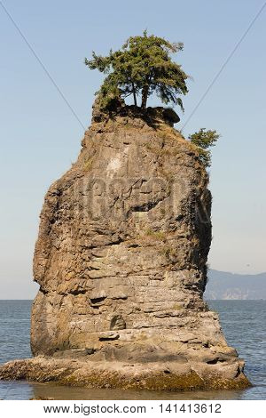 Vancouver Canada - July 24 2016: Portrait of the iconic Siwash Rock which stands in the ocean a few meters off Stanley park. Clear skies