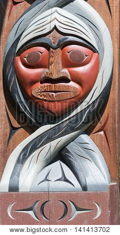 Vancouver Canada - July 24 2016: One of nine totem poles at Hallelujah point in Stanley Park. Portrait of one large wooden mask with maroon face and gray hair on arch.