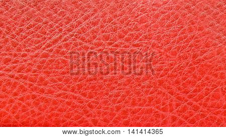 Texture of natural tanned pig skin leather for manufacture of products. Background skin a dimpled red. Raw materials for industry and leather goods.