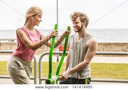 Active woman exercising on elliptical trainer machine and man listening to music. Happy fit sporty girl in training suit working out at outdoor gym. Sport fitness and healthy lifestyle concept.