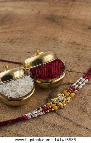 A Rakhi with rice grains and kumkum. An Indian festive background. Raksha Bandhan or Rakhi.