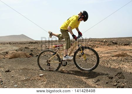 PLAYA BLANCA SPAIN - AUG 3 2006: boy riding his mountainbike offroads and doing tricks