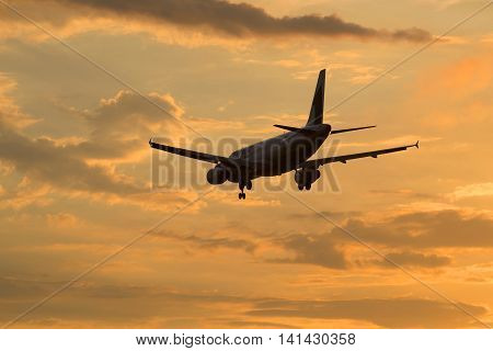 SAINT PETERSBURG, RUSSIA - JULY 03, 2016: Airbus A320-231 (ER-AXO) airlines Fly One flying in sunset sky
