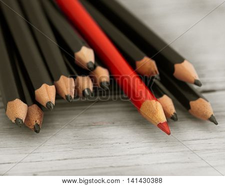 Red pencil stands out from the crowd of black pencil on a wooden white background. Leadership uniqueness independence initiative strategy disagree think different concept of business success
