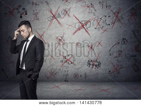 Businessman stands pondering on the concrete background with depicted ideas that crossed with red. Process of thinking. Business plan. Economic analysis. Lack of inspiration. Brainstorming.
