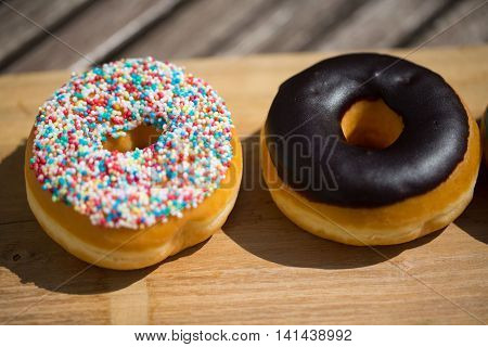 Donut with sprinkles and chocolat , on wooden background