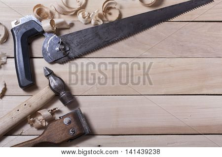 Construction tools on wooden table with sawdust. Joiner carpenter workplace top view. Copy space for text. poster