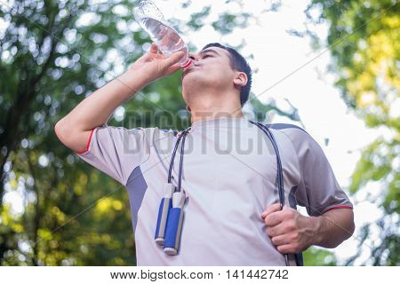 Thirsty athlete drinking water after workout outdoor