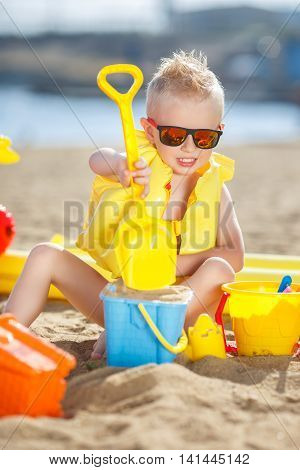 A little boy with short hair and blond hair, dark mirrored sun glasses, a dark blue panties,plays alone in the sand with a yellow shovel,orange and blue bucket and other toys, on the shore of the blue ocean