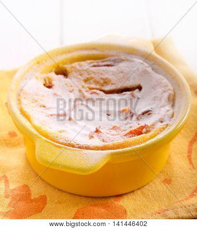 Fruit pudding with icing sugar in ramekin