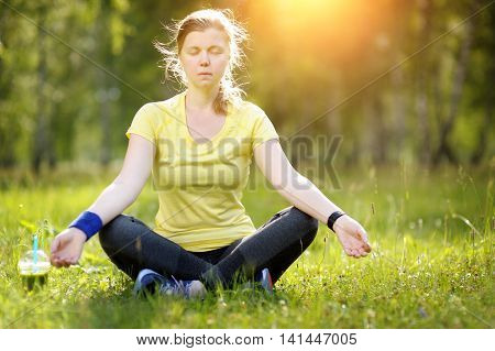 Young Woman In A Lotus Position In A Park.