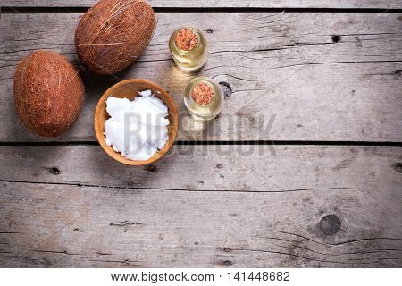 Coconuts and coconut oil on vintage wooden background. Selective focus. Flat lay. Natural organic spa products.Place for text.