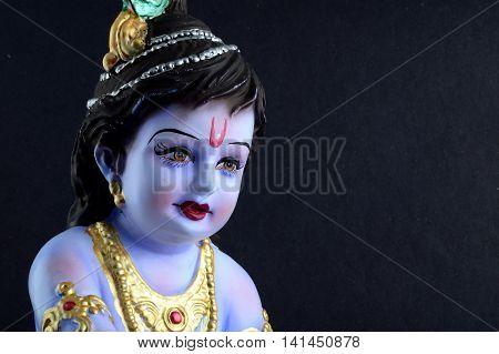 Hindu God Krishna. Statue of God Krishna on dark background