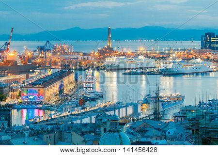 Aerial view of the sea port with night lighting in Genoa at sunset.