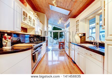 White Kitchen Cabinets With Black Counter Tops In Luxury House.