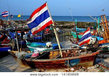 Hua Hin Thailand - December 31 2009: A variety of wooden fishing boats sitting on the sand and shallow waters by the Hua Hin fishing pier